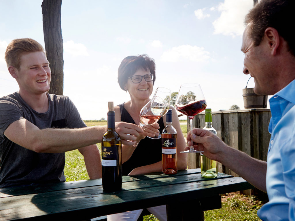 Familie im Garten beim Weintrinken