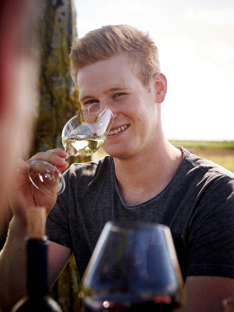 Junger Mann trinkt Wein
