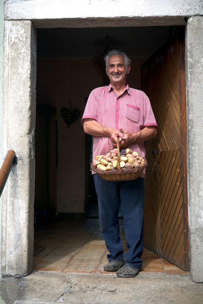 Mann mit Korb voll Erdäpfel