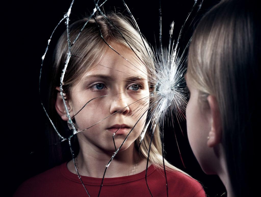Kind vor zerbrochenem Spiegel